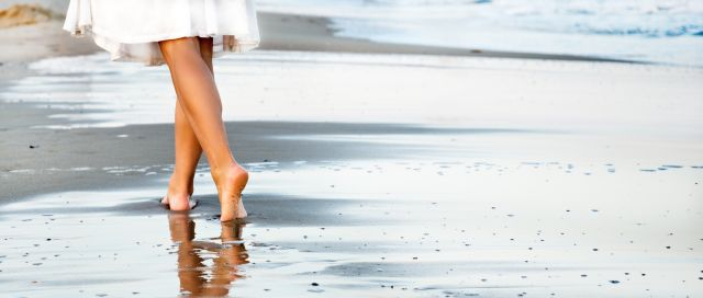 Woman walking on sand beach leaving footprint in the sand