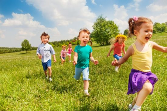 Excited running kids in green field in summer play together