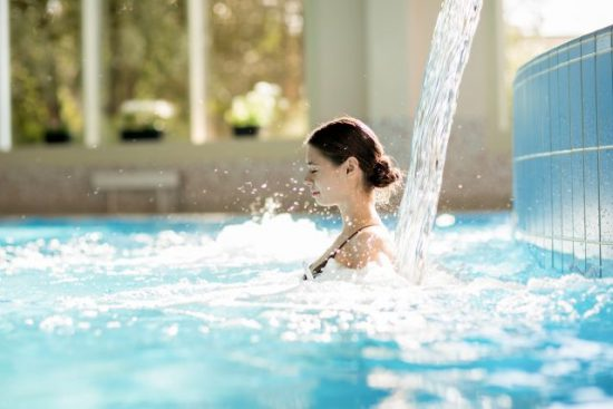 Serene girl enjoying stream of waterfall and its gentle splashes in swimming-pool at spa resort